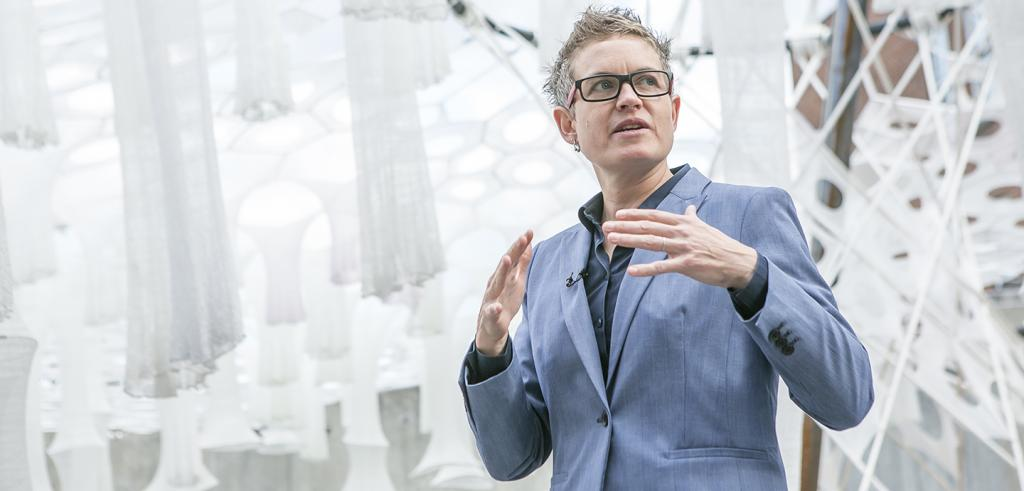 woman in blue suit and glasses gesturing with her hands in front of woven white fabric structures