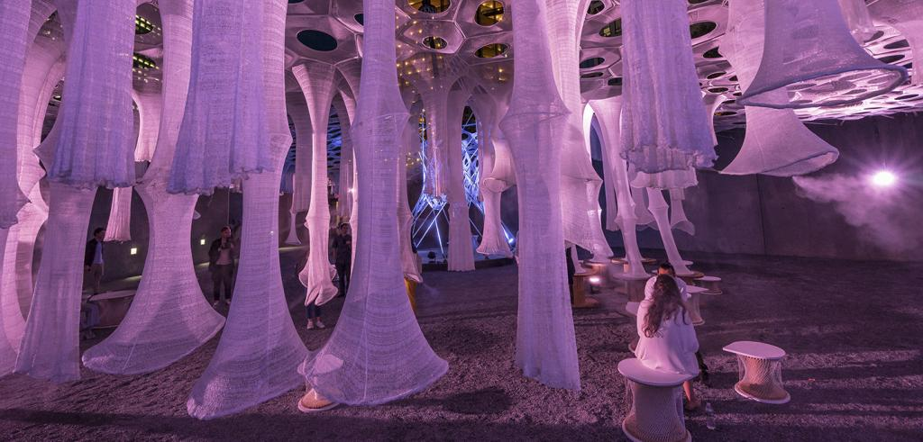 people sitting on stools beneath stalactite-like woven structures that are lit with pink light