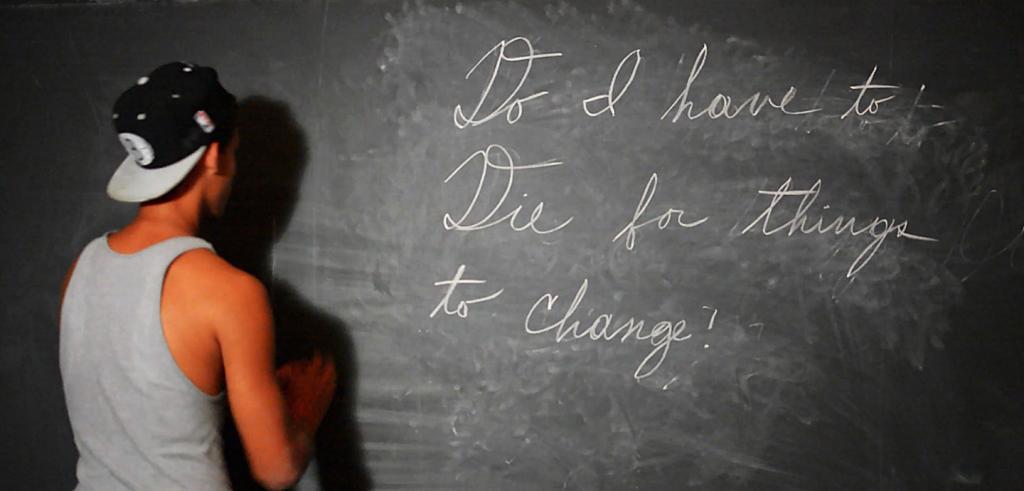 Student writing at blackboard