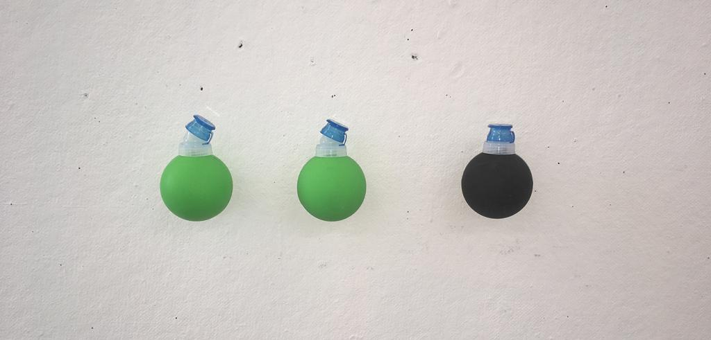 Two neon green balls with a water bottle cap on it next to a black ball with another water bottle cap on it.