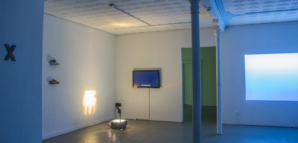 an interior room with white and blue walls, two ceiling support columns, an overhead projector on the floor, an LCD monitor on a wall, and two shoes mounted on another wall.