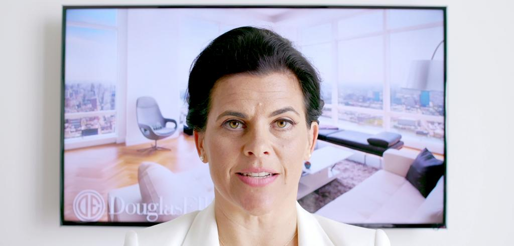 Image of a woman in a white suit standing in front of a photo of an apartment interior