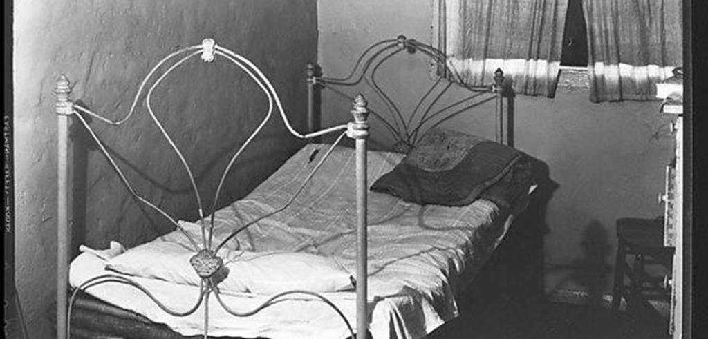 Black and white photograph of an old bed in a small room.