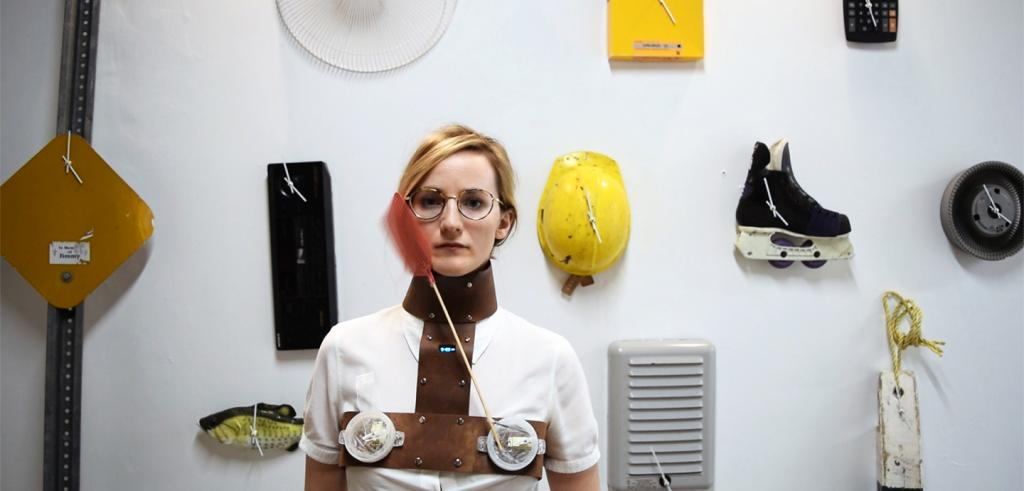 Woman with short blonde hair wearing a handmade device that is strapped to your chest and slaps your face, against a white wall with various inventions.