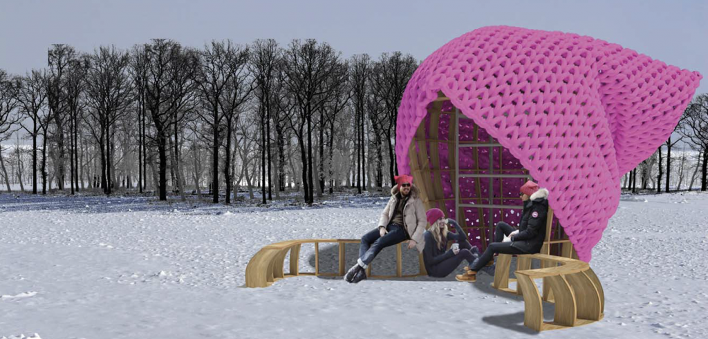 Giant pink pussy hat as a shelter for 3 people and benches on snow with trees in the background