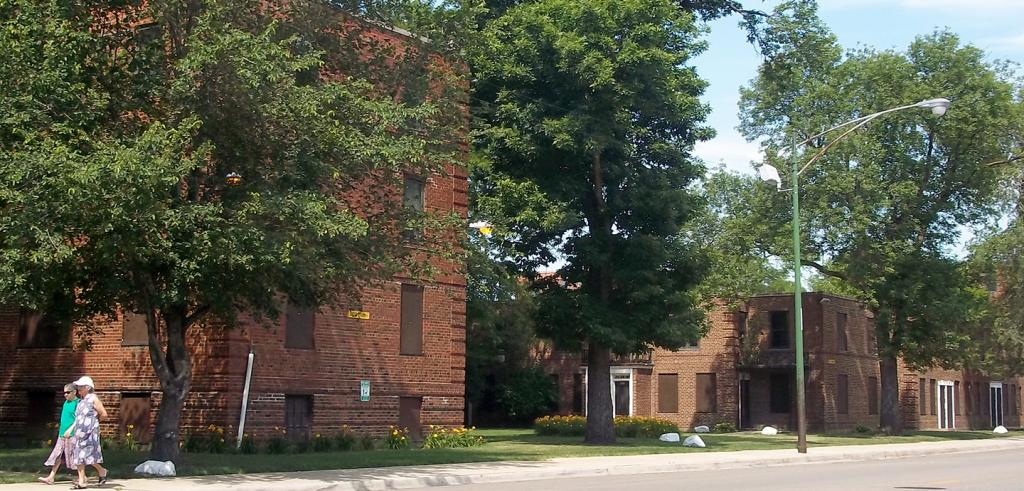 brick apartment buildings with trees and two people walking along the sidewalk