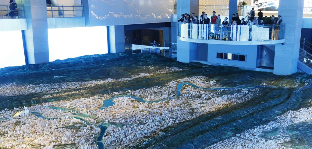 People on a balcony overlooking a 3D model of a city and two rivers
