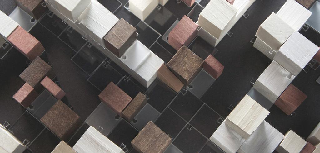 model of black, white, and brown cubes of wood arranged as a city with different sized buildings