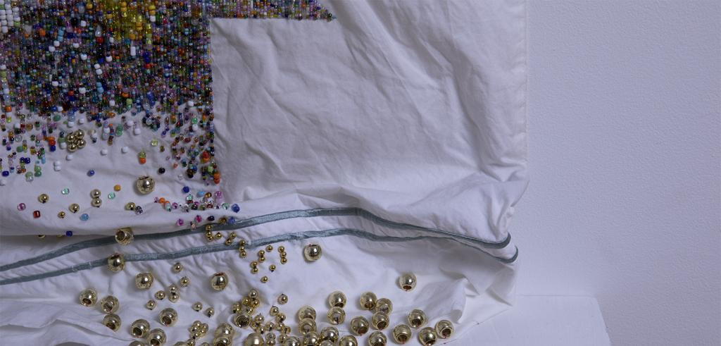 White pillow case with different colored beads in the top left corner with larger gold beads in the bottom center.