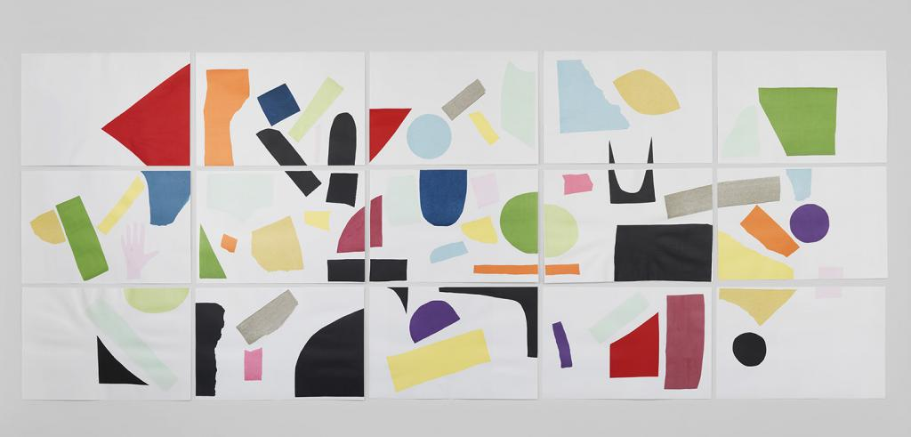 Colorful geometrical shapes in red, orange, blue, purple, green, yellow, and black on fifteen pieces of white paper arranged on a wall in a rectangle