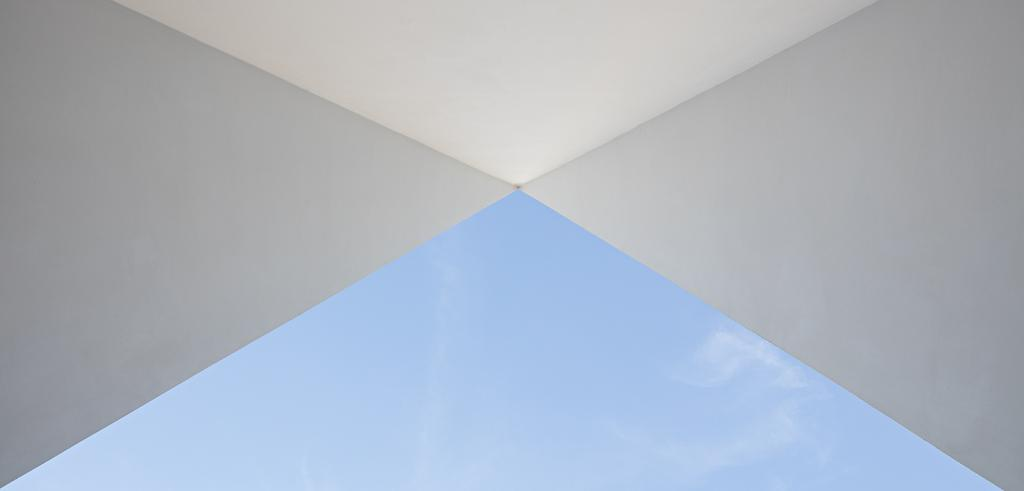 an angled ceiling with a triangular skylight showing blue sky and wispy clouds
