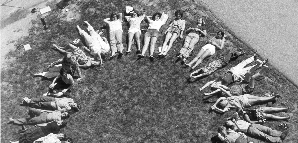 black and white photo of aerial view of women lying on the grass creating a female symbol in 1975