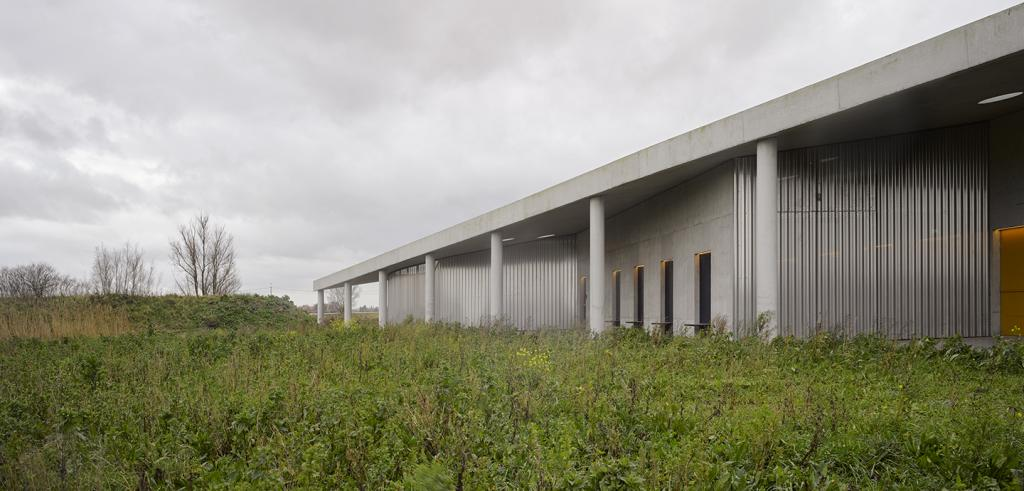 Grey building with columns, green grass, cloudy sky.
