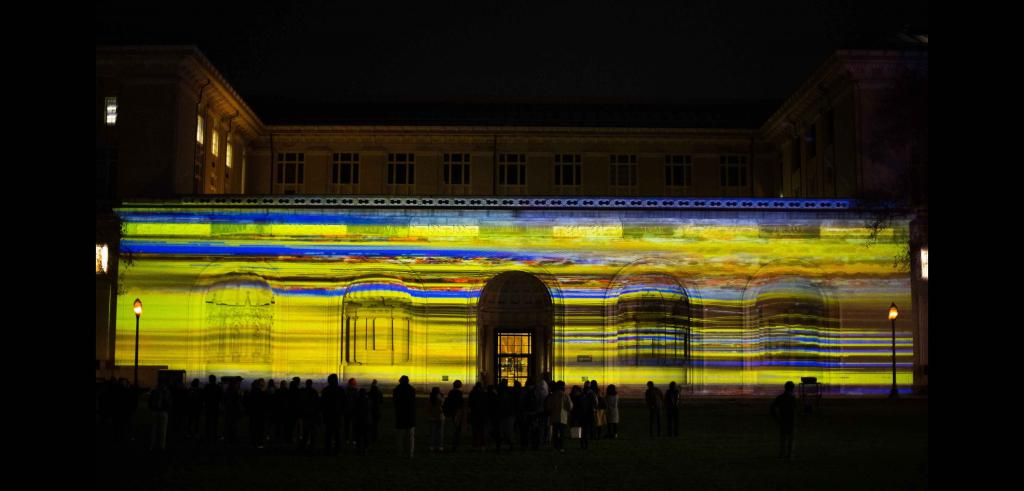 Illuminated building with bright stripes of yellow, blue, and some orange with a group of onlookers in front at night.
