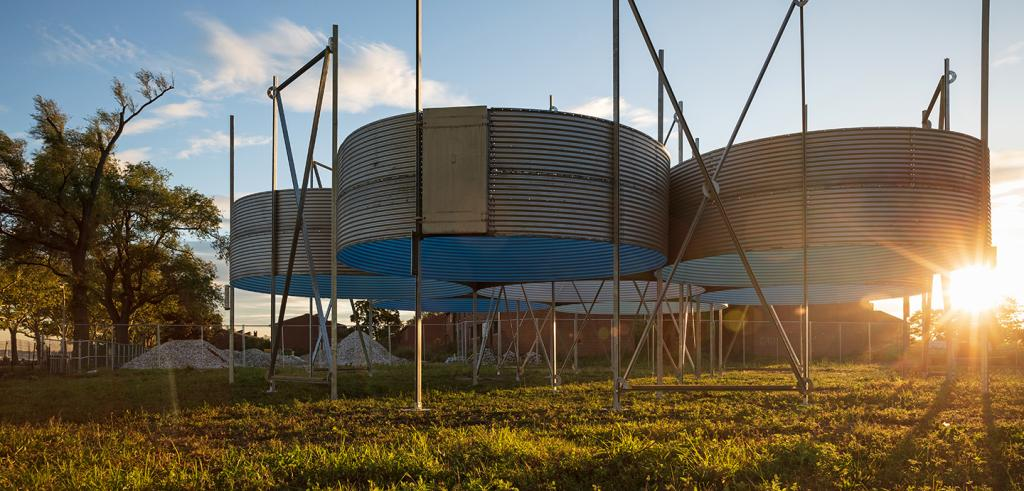 Six circular sections of corrugated metal grain silos grouped together with the sun setting behind them