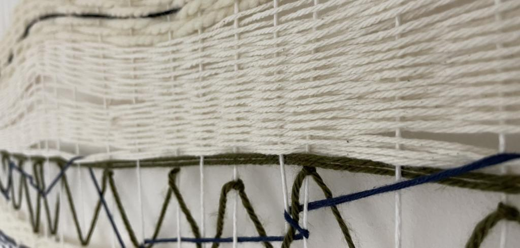 White yarn tapestry with stripes of dark brown and one dark blue piece.