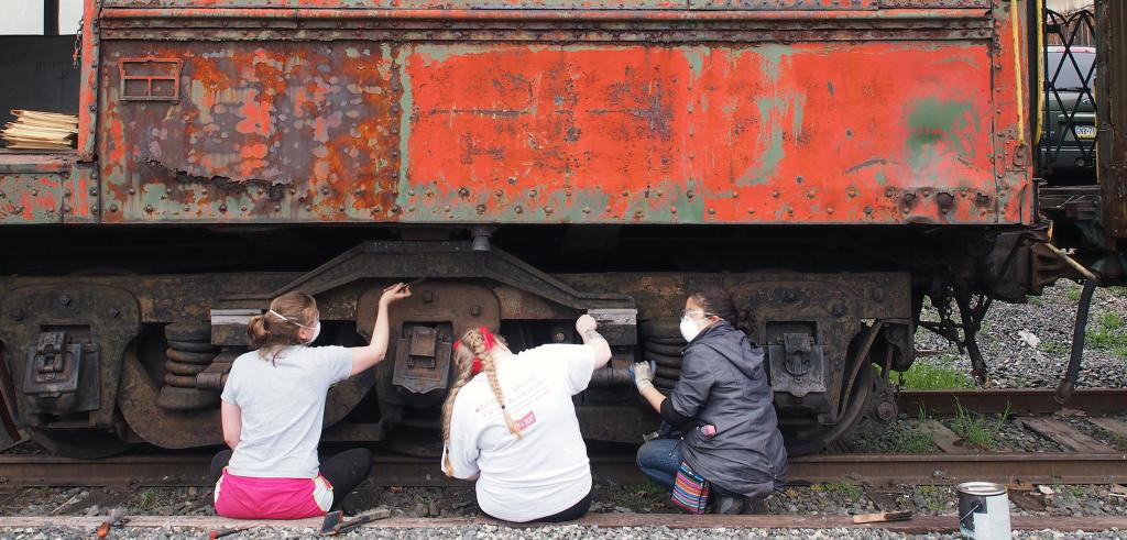 three students sand a rusted railroad car