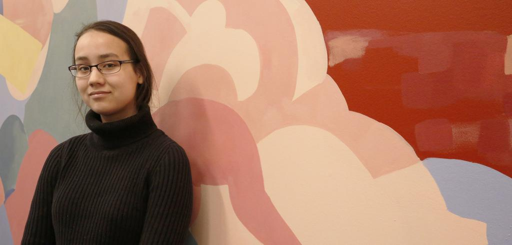 Art student stands in front of a mural she painted