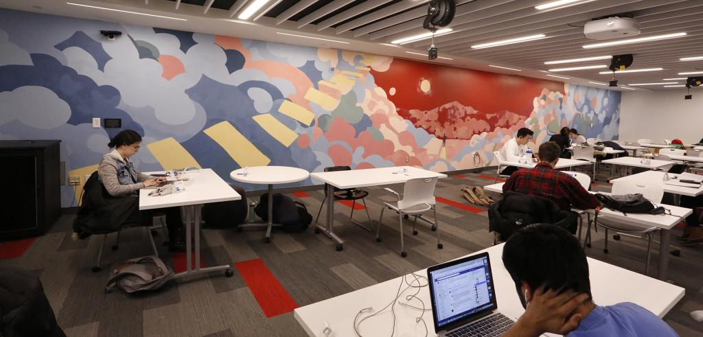 People seated at tables work on laptops in an office space beside a colorful mural