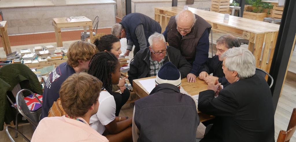 A small group of young people and elderly looking at papers on a table