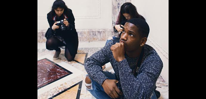 Three young people with cameras kneel on a mosaic tiled floor.