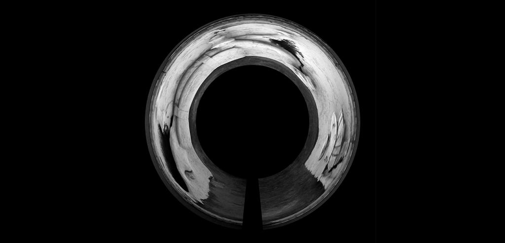 A reflective silver circle on a black background