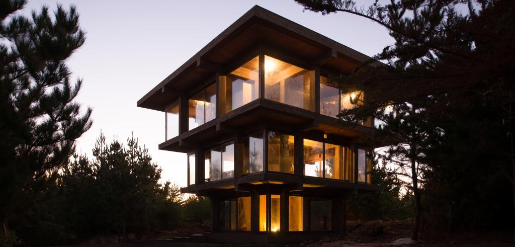 Inverted pagoda house at dusk with lights on inside
