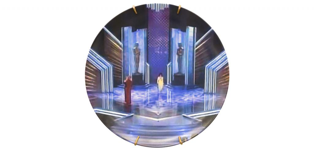Circular image of an old awards stage with one woman walking in the middle wearing a yellow dress and a woman to the left in a red dress.