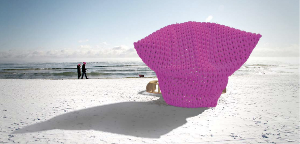 Two people walking on a snow-covered beach and a large pink pussy hat in the foreground casting a shadow