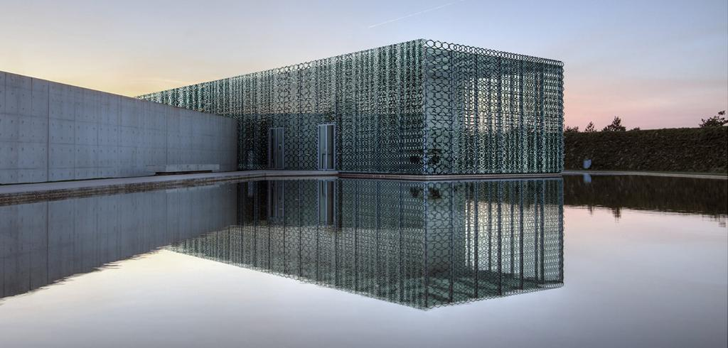 a concrete and lattice-work building with its reflection in a pool