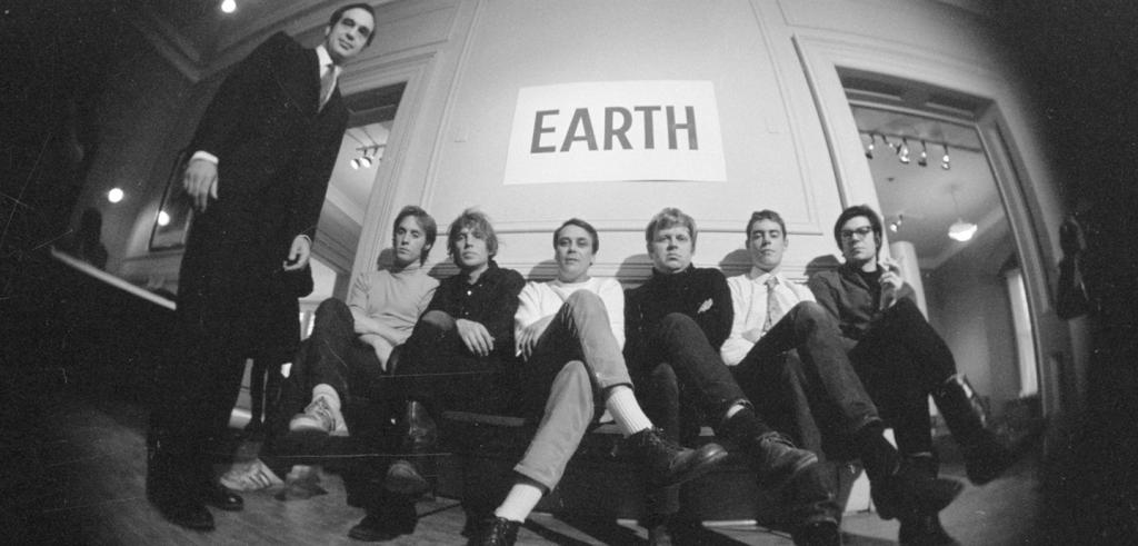 a group of men in 60s-era clothing seated under a sign that says Earth, captured in a fish-eye view.