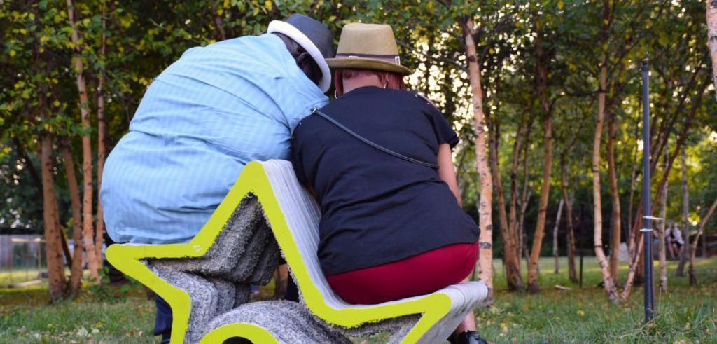 Two people share a concrete, star-shaped seat in a park with trees in the background
