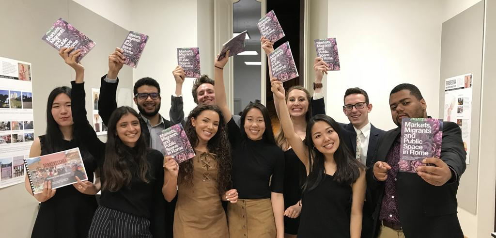 A group of students each holding up a publication.