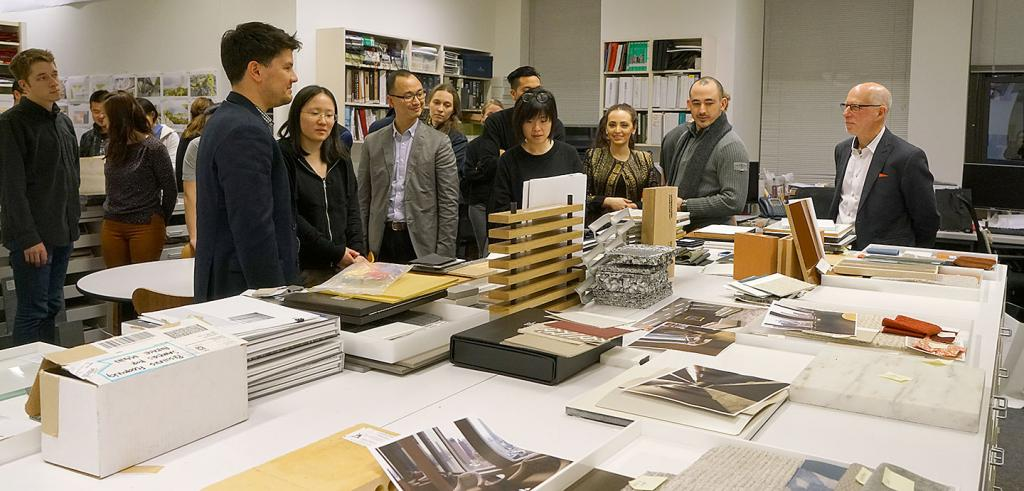 students and SOM guide around a table filled with models and designs