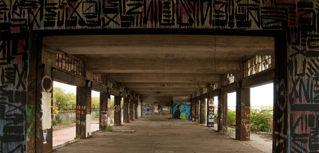 View through the middle of a bridge underpass with columns covered in graffiti and other markings.