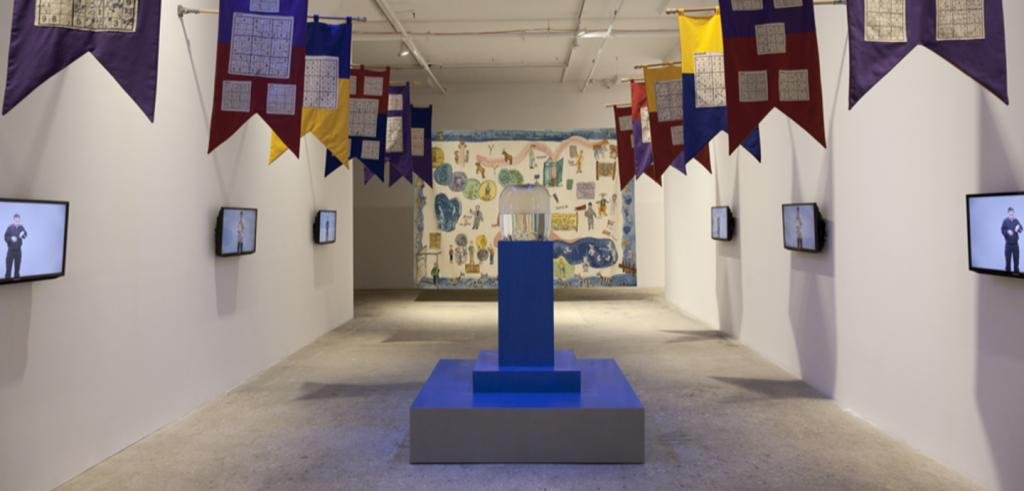 gallery view of tv screens, sculpture, and banners