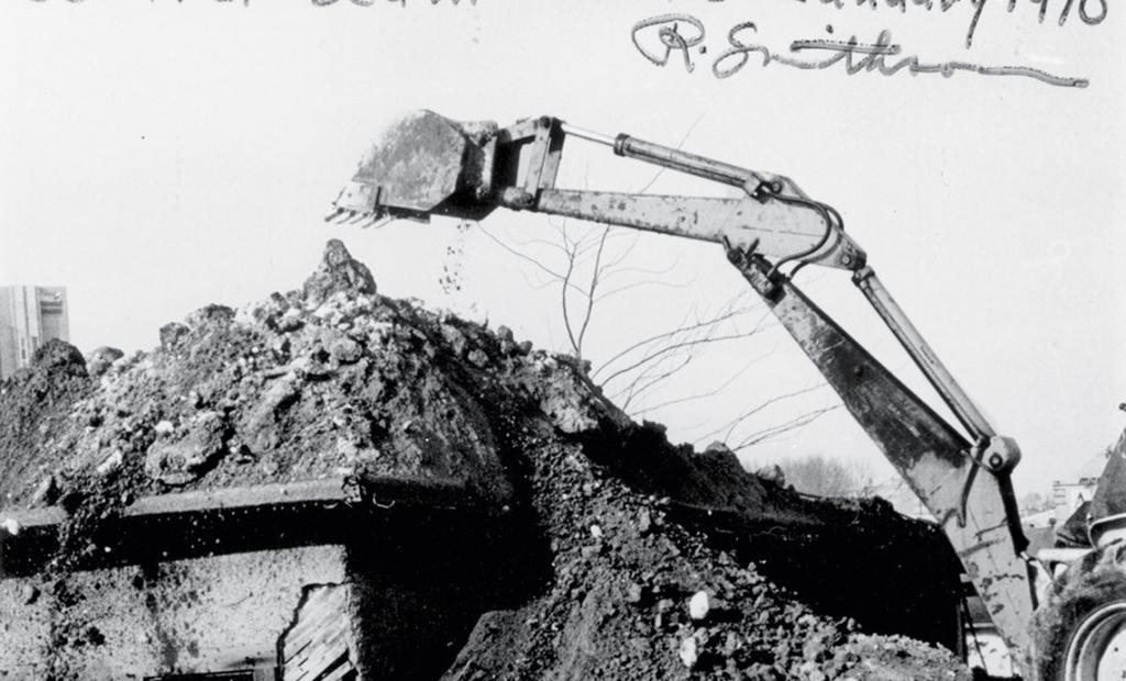 Black and white film photograph of an excavator moving soil.