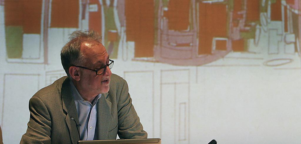 man with gray hair and glasses leans on a podium, an orange, green, and white cityscape sketched behind him.