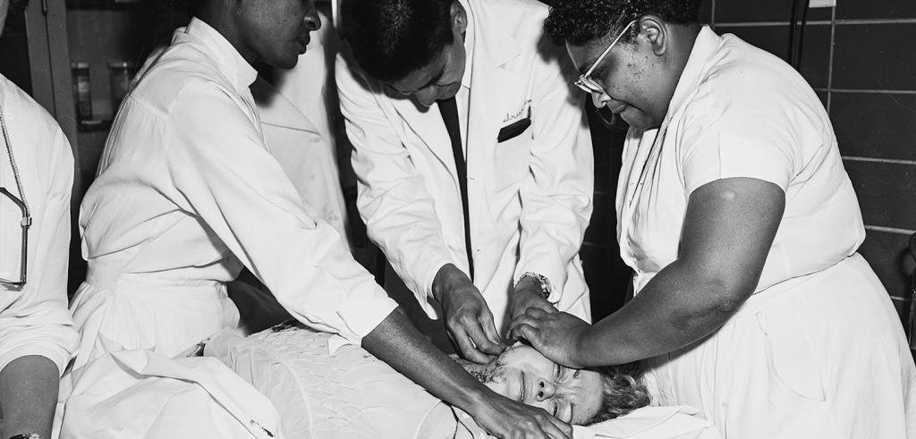 Black and white photo of doctors and nurses helping a female patient lying on a bed