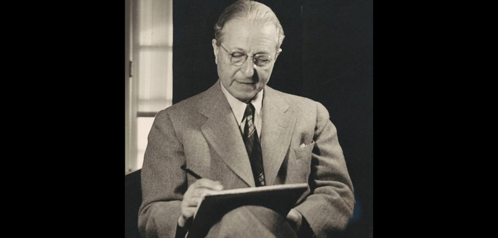 Man seated in a dark chair, wearing a light suit