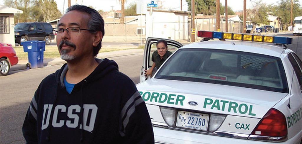 Image of a man standing near the road with a border patrol agent getting out of her car.
