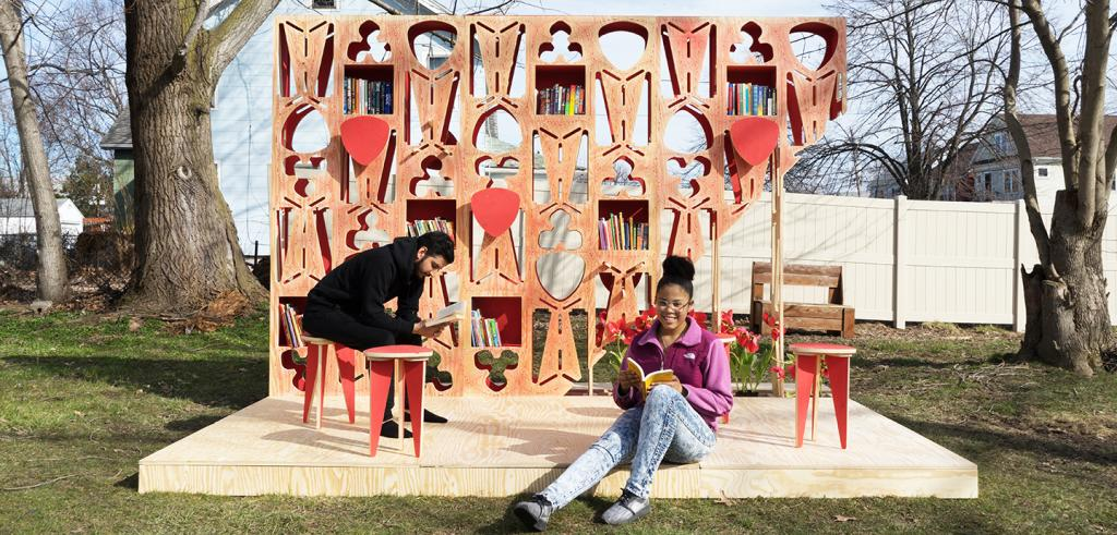 2 people in a suburban park sit on a wooden platform reading books, a tall wooden panel behind them is decorated with cutouts and geometric shapes