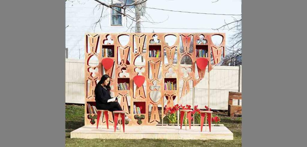 A woman seated on one of four red stools reads a book in front of a wooden panel of cutout geometric shapes.