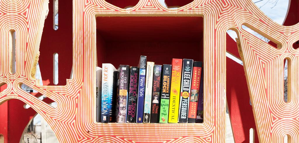 Twelve books shelved in a cubby hole within a wooden display decorated with red lines.