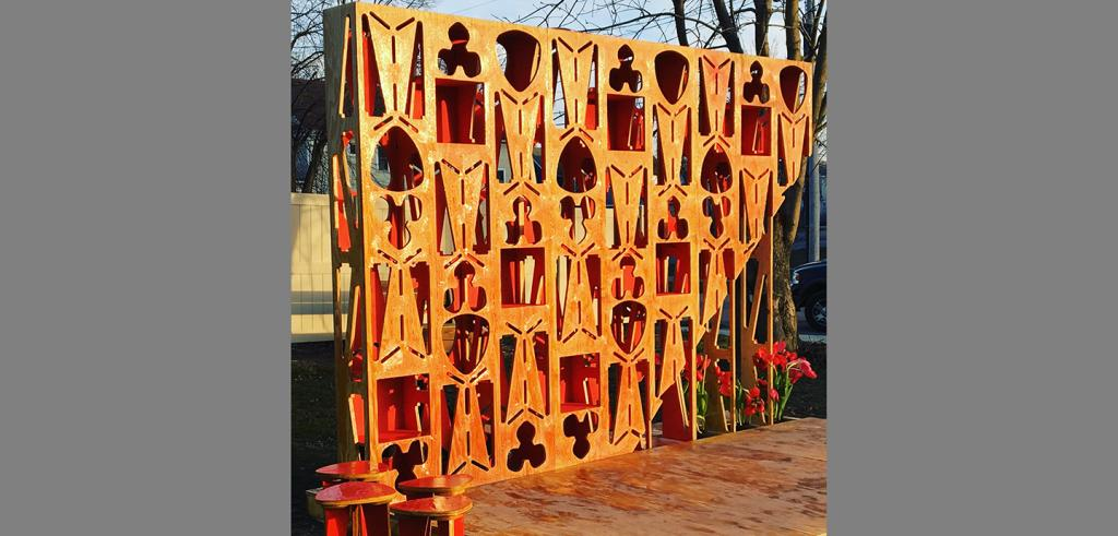 A 3-dimensional wooden display panel of cutouts in geometric shapes, red tulips, and four stools set in slanting sunlight.
