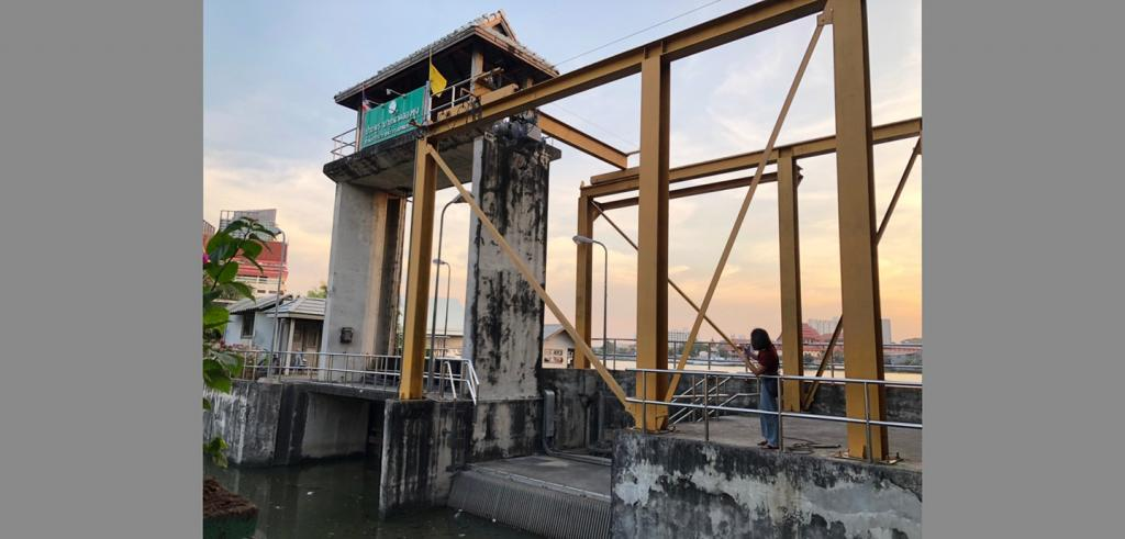 A woman stands near a tall concrete and steel structure above a sluice gate on a river