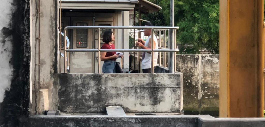 Two people talking behind a metal gate in a concrete structure.