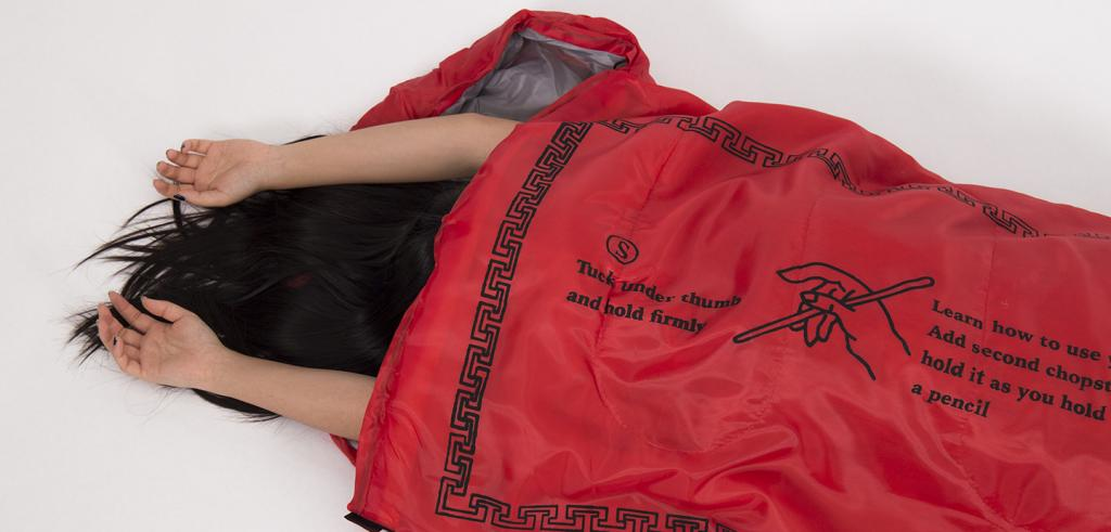 Someone with long dark hair and arms sticking out of a chopsticks wrapper sleeping bag.