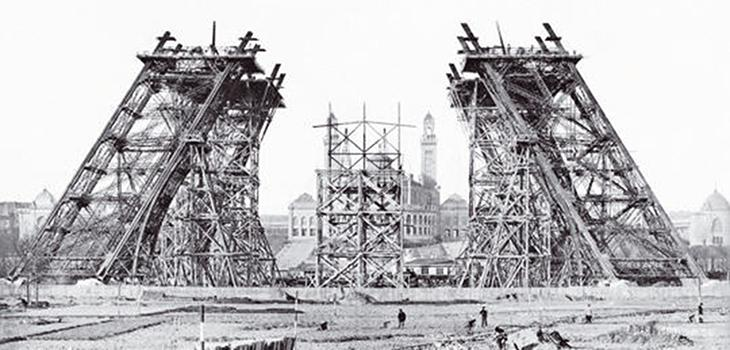 The two towers that form the base of the Eiffel tower under construction