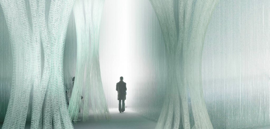 Silhouette of a person walking between translucent fiber columns
